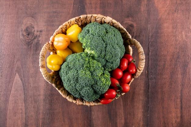 Bovenaanzicht verse broccoli cherry tomaat en gele peper in mand op houten oppervlak