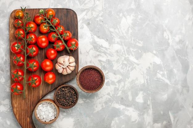 Bovenaanzicht verse cherrytomaatjes met verschillende kruiden op licht-wit oppervlak