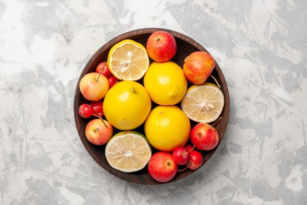 Bovenaanzicht verse citroenen geheel en gesneden op witte ruimte