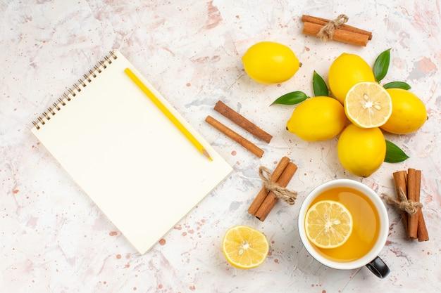 Bovenaanzicht verse citroenen gesneden citroen kaneelstokjes een kopje citroenthee notebook op helder geïsoleerd oppervlak
