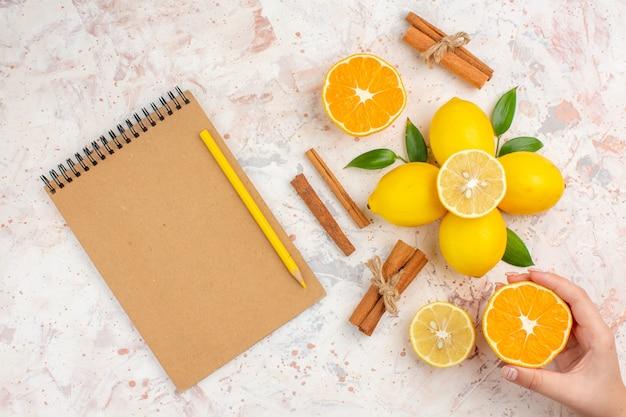 Bovenaanzicht verse citroenen gesneden oranje kaneelstokjes gesneden sinaasappel in vrouwelijke hand notebook potlood op heldere geïsoleerde oppervlak