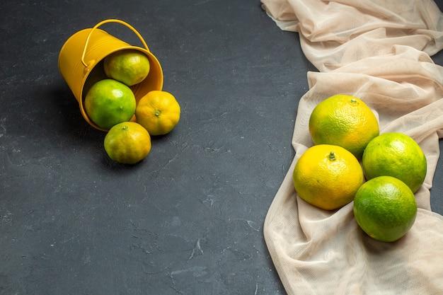 Bovenaanzicht verse citroenen op beige tule sjaal citroenen verspreid uit emmer op donkere ondergrond met kopie ruimte