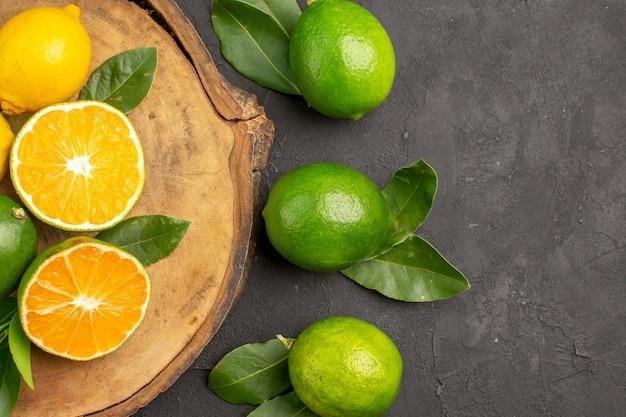 Bovenaanzicht verse citroenen op donkere tafel limoen zure vruchten citrus