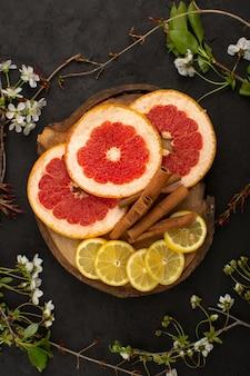 Bovenaanzicht verse citrusvruchten zacht gesneden samen met kaneel in het donker