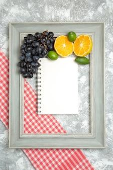 Bovenaanzicht verse donkere druiven met sinaasappels en feijoa binnen frame op wit oppervlak fruit rijp zacht vers