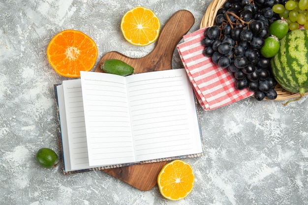 Bovenaanzicht verse donkere druiven met sinaasappels en watermeloen op wit oppervlak rijp fruit mellow tree verse vitamine Gratis Foto