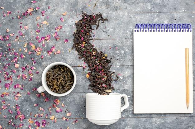 Bovenaanzicht verse droge thee met blocnote op grijs bureau