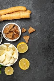Bovenaanzicht verse druiven met kaasgroenten en schijfjes citroen op donkere oppervlakte maaltijd ontbijtschotel melk fruit
