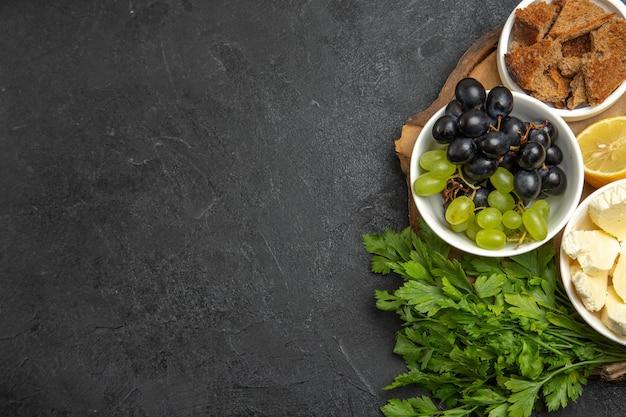 Bovenaanzicht verse druiven met witte kaas greens en citroen op donkere oppervlakte maaltijd fruit melk voedsel