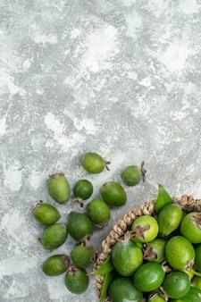 Bovenaanzicht verse feijoas in rieten mand op grijze geïsoleerde oppervlakte vrije plaats