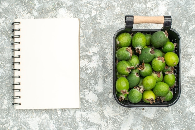 Bovenaanzicht verse feykhoas in mand notebook op grijs oppervlak