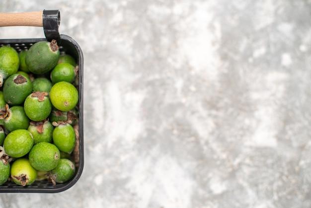 Bovenaanzicht verse feykhoas in mand op grijze ondergrond met kopie ruimte