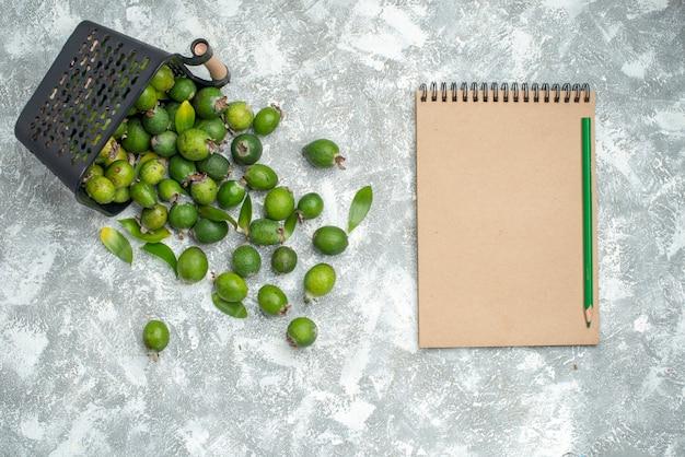 Bovenaanzicht verse feykhoas verspreid van mand notebook en groen potlood op grijs oppervlak
