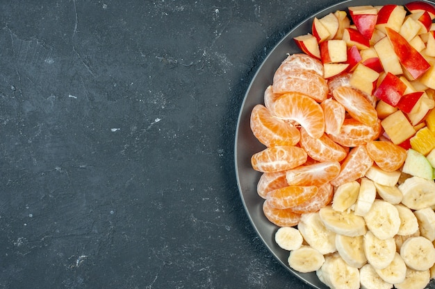 Bovenaanzicht verse fruitsalade gesneden bananen, appels en sinaasappels op donkere achtergrond