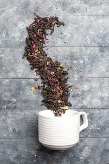 Bovenaanzicht verse gedroogde thee binnen en buiten kopje op het grijze rustieke bureau