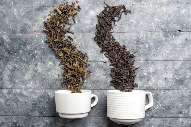 Bovenaanzicht verse gedroogde thee binnen en buiten kopjes op grijs rustiek bureau