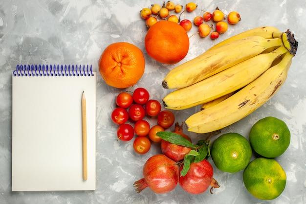 Bovenaanzicht verse gele bananen met granaatappels kladblok en mandarijnen op lichtwit bureau