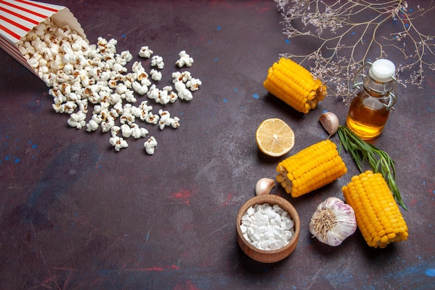 Bovenaanzicht verse gele likdoorns met popcorn op donkere bureau maïs snack eten rauw vers