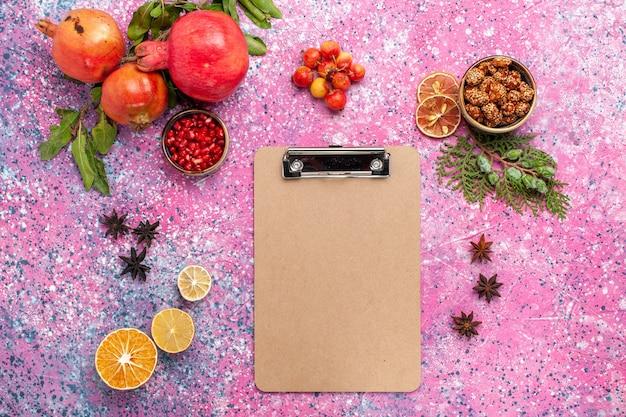 Bovenaanzicht verse granaatappel met blocnote op roze oppervlak