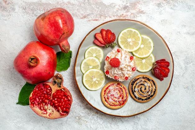Bovenaanzicht verse granaatappel met cake en plakjes citroen op witte ruimte