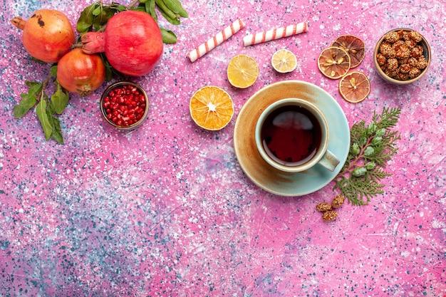 Bovenaanzicht verse granaatappel met groene bladeren en kopje thee op het roze bureau