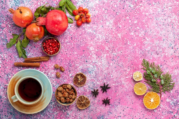 Bovenaanzicht verse granaatappel met groene bladeren en kopje thee op het roze oppervlak