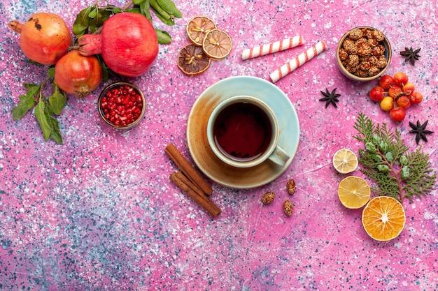 Bovenaanzicht verse granaatappel met groene bladeren en kopje thee op lichtroze oppervlak