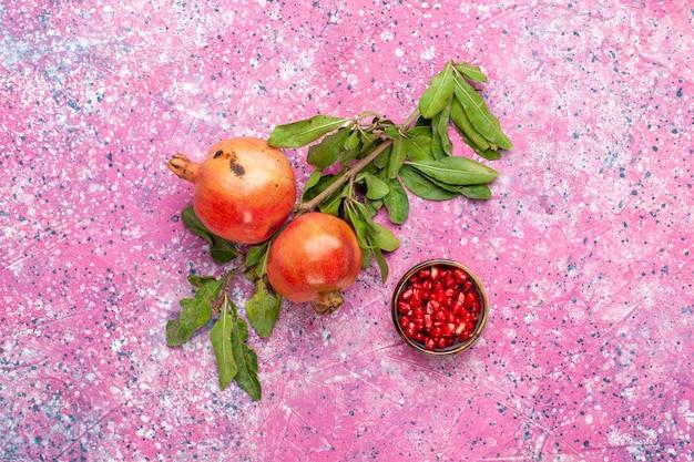 Bovenaanzicht verse granaatappel met groene bladeren op roze oppervlak