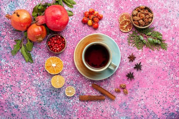 Bovenaanzicht verse granaatappel met kaneel en kopje thee op roze oppervlak
