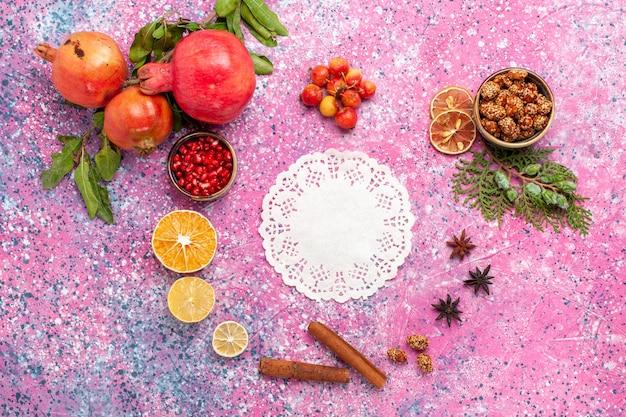 Bovenaanzicht verse granaatappel met kaneel op het roze oppervlak