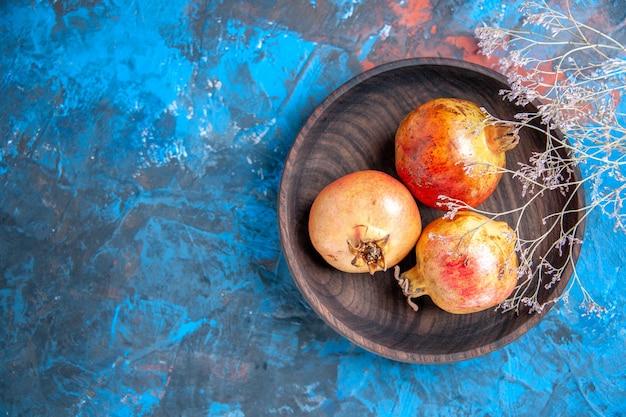 Bovenaanzicht verse granaatappels in een kom op blauwe achtergrond