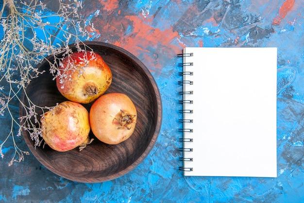 Bovenaanzicht verse granaatappels in houten kom een notitieboekje op blauwe achtergrond
