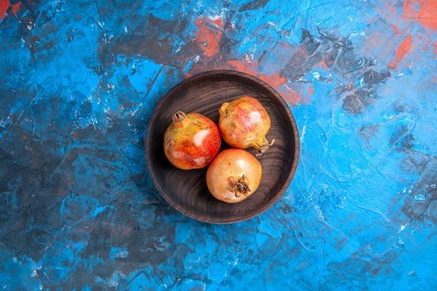Bovenaanzicht verse granaatappels in houten kom op blauwe achtergrond met kopie ruimte