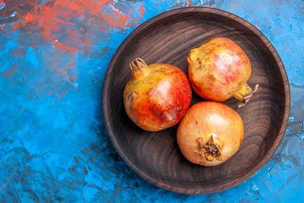 Bovenaanzicht verse granaatappels in houten kom op blauwe achtergrond
