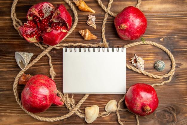 Bovenaanzicht verse granaatappels met touwen op bruin bureau