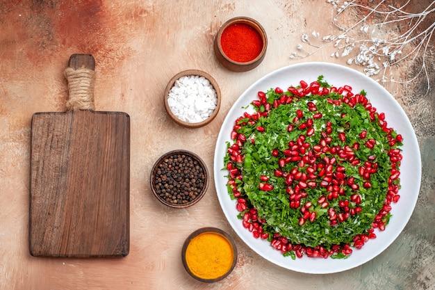 Bovenaanzicht verse greens met gepelde granaatappels op lichte tafel maaltijd fruit kleur greens