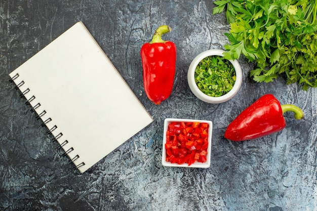 Bovenaanzicht verse greens met rode paprika op de lichtgrijze tafel
