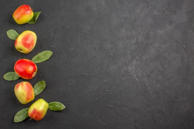 Bovenaanzicht verse groene appels met groene bladeren op een donkere tafel mellow tree rijp vers