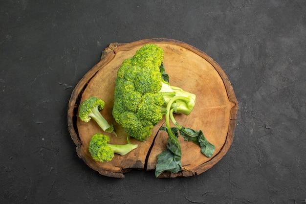 Bovenaanzicht verse groene broccoli plant uit kool op donkere tafelsalade rijpe gezondheid