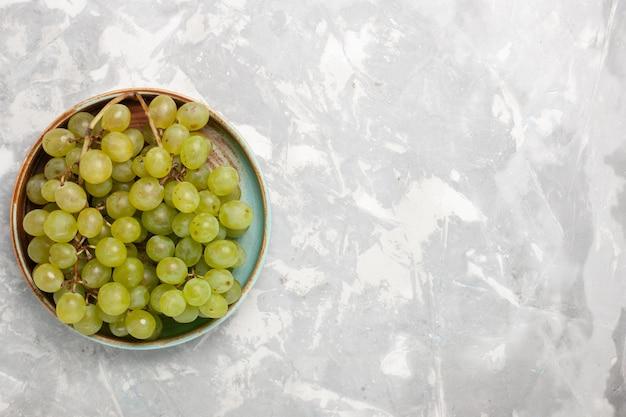 Bovenaanzicht verse groene druiven binnen op wit oppervlak