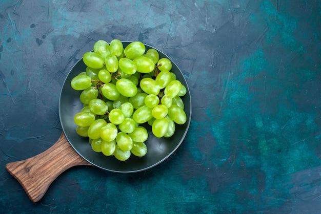 Bovenaanzicht verse groene druiven, zacht en sappig fruit in plaat op donkerblauwe achtergrond.