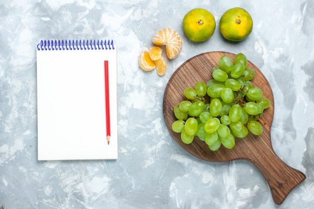 Bovenaanzicht verse groene druiven, zacht sappig fruit met mandarijnen op het lichtbureau.