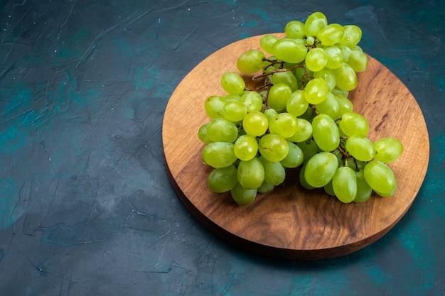 Bovenaanzicht verse groene druiven, zacht sappig fruit op het donkerblauwe bureau.