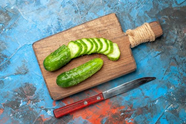 Bovenaanzicht verse groene komkommers gesneden op de blauwe achtergrond