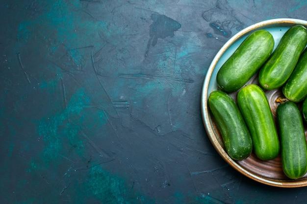 Bovenaanzicht verse groene komkommers rijpe groenten in plaat op het donkerblauwe bureau.