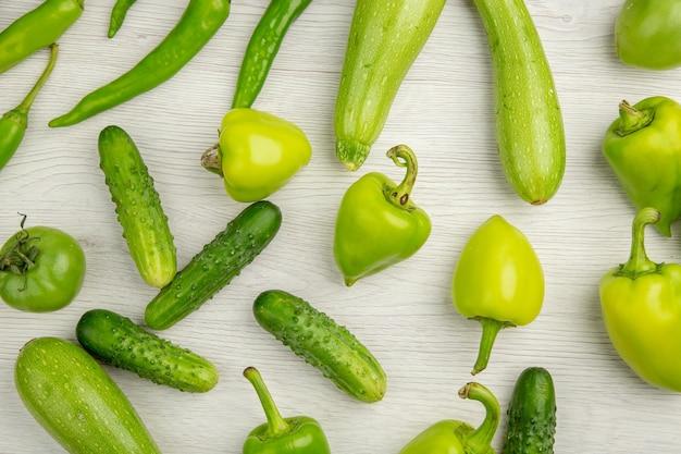 Bovenaanzicht verse groene paprika's met groene komkommers en tomaten op wit bureau kleur rijpe salade foto maaltijd hot