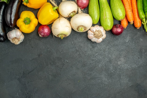 Bovenaanzicht verse groenten aubergines paprika en andere groenten op een donkere achtergrond