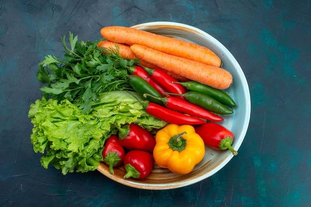 Bovenaanzicht verse groenten binnen plaat op het blauwe bureau snack lunch salade plantaardig voedsel