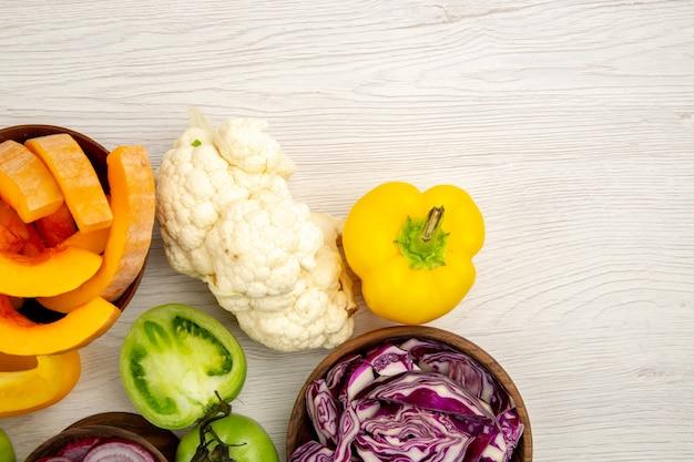 Bovenaanzicht verse groenten gesneden groene tomaten gesneden rode kool pompoen gesneden in kommen op oppervlak met vrije plaats