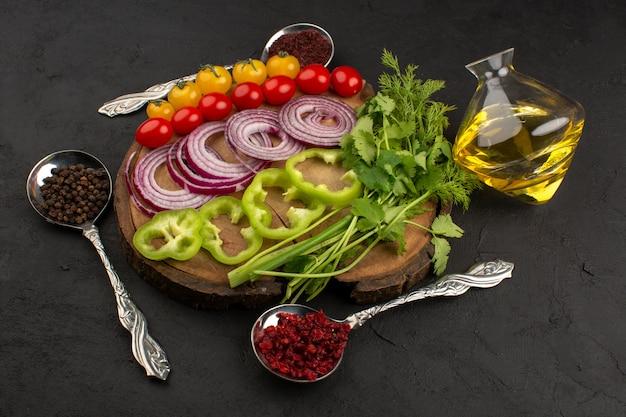 Bovenaanzicht verse groenten in plakjes gesneden en heel kleurrijk zoals uien en groene paprika op het bruine bureau en grijs